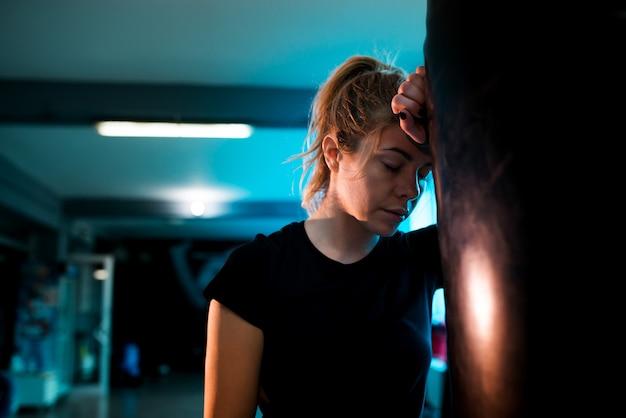 Porträt des boxermädchens ermüdete nach der ausbildung mit schwerem sandsack in der turnhalle.