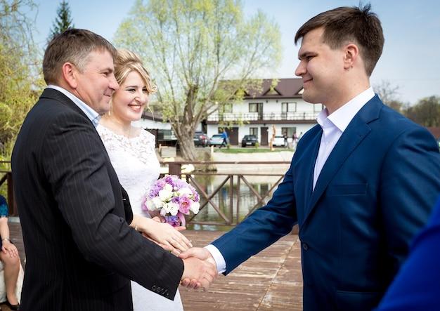 Porträt des brautvaters, der dem bräutigam bei der hochzeitszeremonie die hand schüttelt