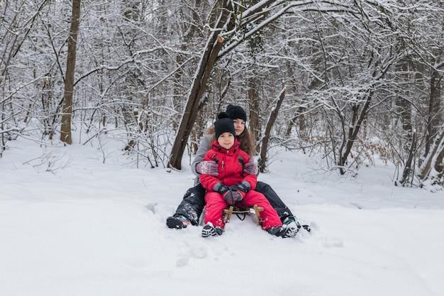 Porträt des bruders und der schwester, die auf hölzernem schlitten in der schneebedeckten landschaft sitzen