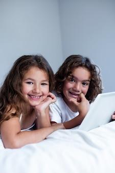 Porträt des bruders und der schwester, die digitale tablette verwendet