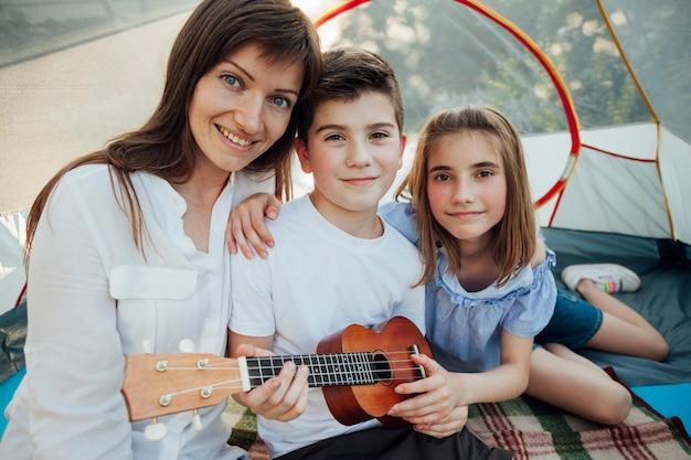 Porträt des bruders und der schwester, welche die ukulele sitzt mit ihrer mutter im zelt hält