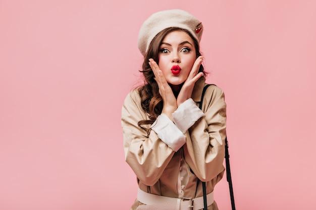 Porträt des brünetten mädchens, das kuss bläst. grünäugige dame in baskenmütze und trenchcoat, die auf rosa hintergrund aufwirft.