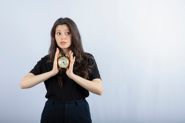 Porträt des brünetten mädchens im schwarzen outfit, das uhr hält und auf grau aufwirft