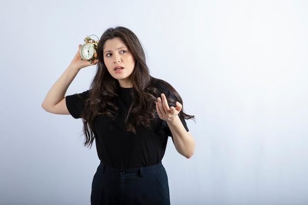 Porträt des brünetten mädchens im schwarzen outfit, das uhr hält und zur kamera aufwirft.