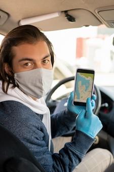 Porträt des brünetten taxifahrers in der maske und in den handschuhen, die auf online-karte auf smartphonebildschirm zeigen, während passagier nach zielort fragen