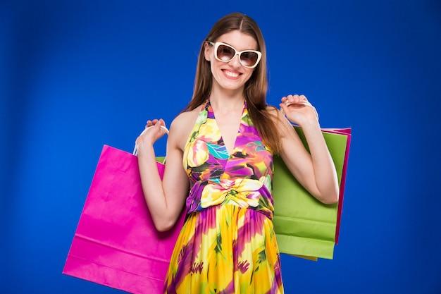 Porträt des brunette in der sonnenbrille mit paketen