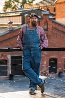 Porträt des brutalen bärtigen motorradreparaturmanns, der blaue overalls trägt