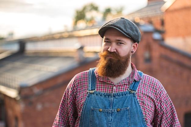 Porträt des brutalen bärtigen stilvollen handwerkers, der blaue overalls trägt