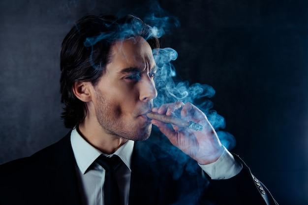 Porträt des brutalen gutaussehenden mannes mit stoppeln, die eine zigarre rauchen