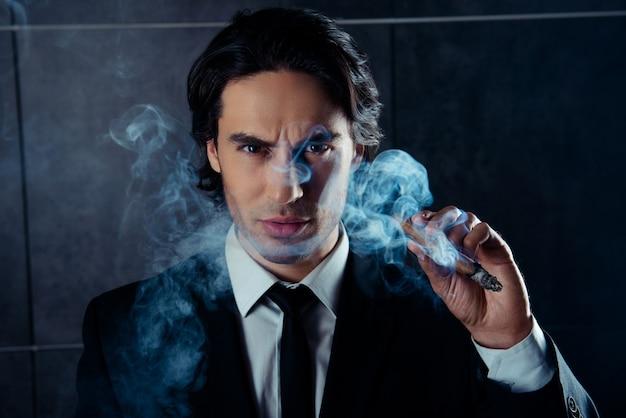 Porträt des brutalen machomannes, der zigarre mit rauch hält