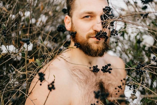 Porträt des brutalen nackten mannes des ingwers mit bart, der zwischen büschen aufwirft