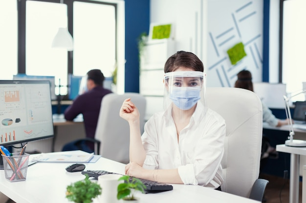 Porträt des büroangestellten, der einen gesichtsschutz trägt. geschäftsteam, das in einem finanzunternehmen arbeitet und die soziale distanz während der globalen pandemie respektiert.