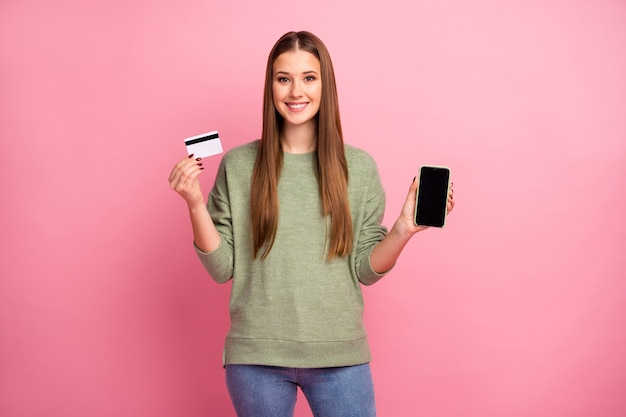 Porträt des charmanten fröhlichen hübschen mädchens halten smartphone-kreditkarte