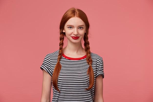 Porträt des charmanten hübschen schönen mädchens mit den roten lippen der rothaarigen zöpfe, nettes lächeln, gekleidet in abgestreiftem t-shirt, isoliert