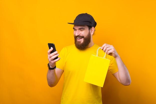 Porträt des charmanten jungen bärtigen mannes, der einkaufstasche hält und smartphone verwendet
