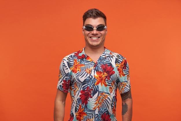 Porträt des charmanten jungen dunkelhaarigen mannes, der in der schutzbrille aufwirft, aufgeregt über das schwimmen schaut und breit lächelt
