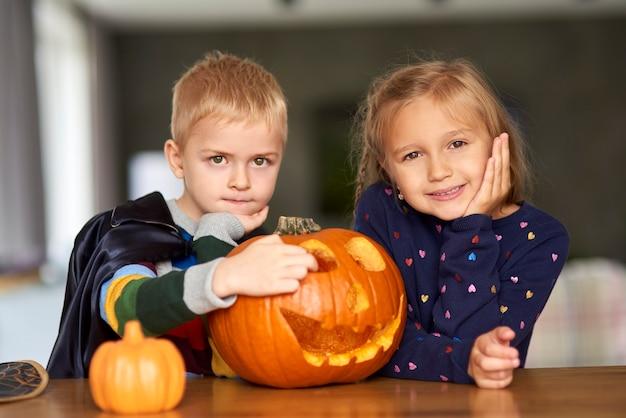 Porträt des charmanten kleinen jungen und des mädchens mit halloween-kürbis