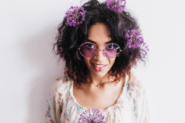 Porträt des charmanten schwarzen mädchens, das mit allium aufwirft. innenfoto des hübschen afrikanischen weiblichen modells, das lila blumen hält und lächelt.