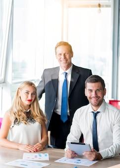 Porträt des chefs mit seinen zwei kollegen am arbeitsplatz im büro