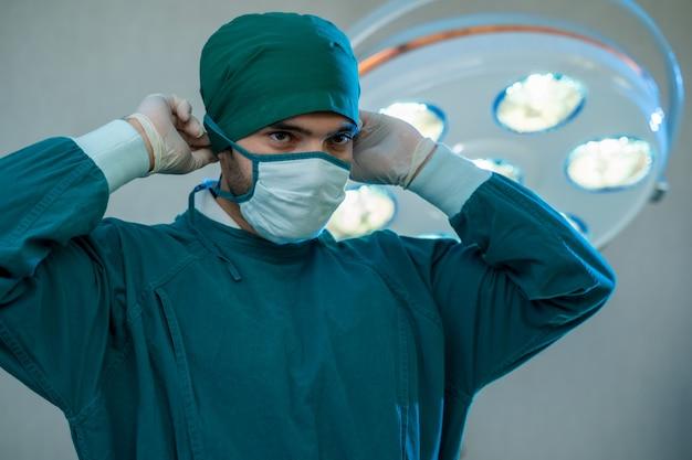 Porträt des chirurgen, der im operationssaal steht, bereit, an einem patienten zu arbeiten, medizinischer arbeiter in der chirurgischen uniform im operationssaal in einem krankenhaus.