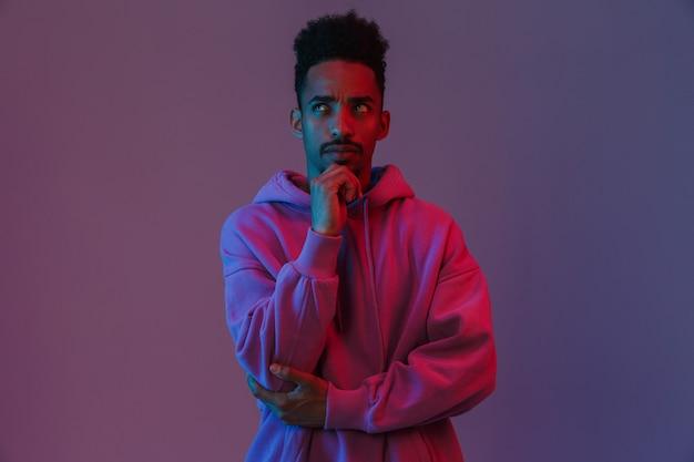 Porträt des denkenden afroamerikanischen mannes in buntem hoodie posiert und nach oben schauend isoliert über violette wand