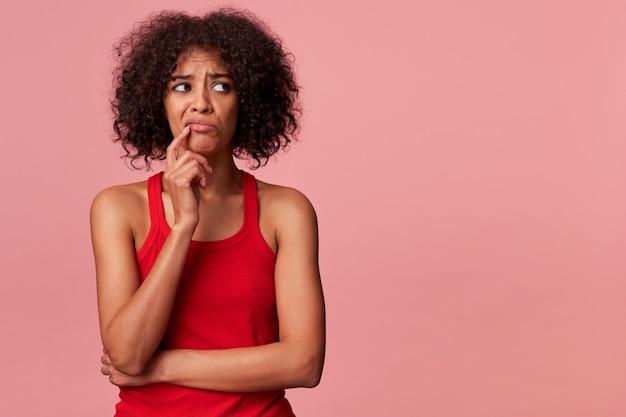 Porträt des denkenden jungen afroamerikanischen mannes mit dem gelockten dunklen haar, das ein rotes t-shirt trägt. der finger berührt die lippen und schaut isoliert mit dem copyspace weg.