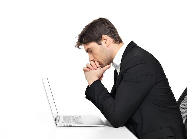 Porträt des denkenden jungen büroangestellten mit laptop, der auf tisch lokalisiert auf weiß sitzt.
