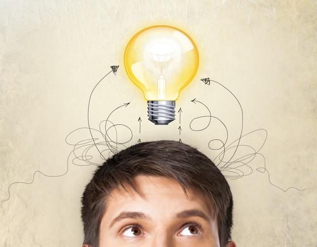 Porträt des denkenden mannes und der lampe über dem kopf