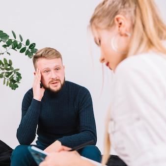 Porträt des deprimierten männlichen patienten, der mit weiblichem psychologen spricht