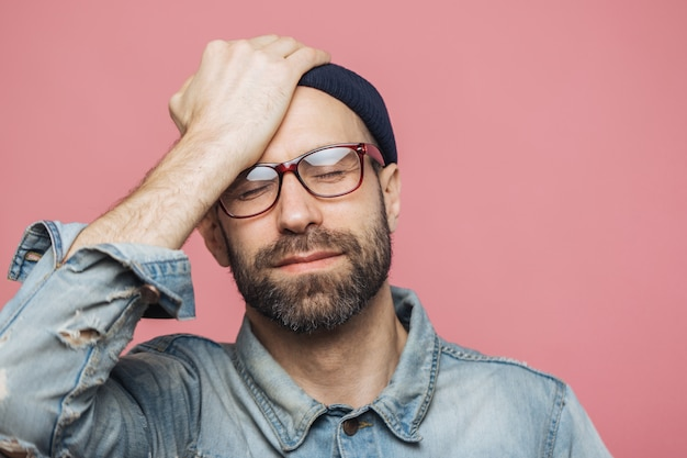 Porträt des deprimierten mitte gealterten unrasierten mannes schließt augen und hält hand auf stirn