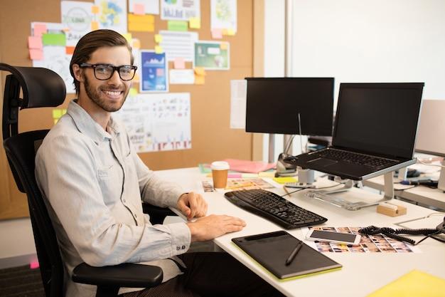Porträt des designers, der am kreativen büro sitzt