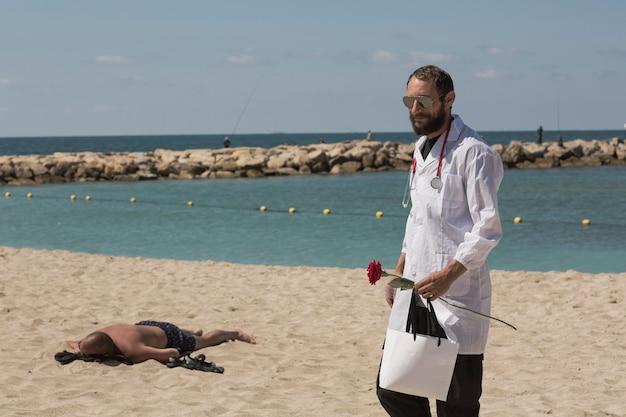 Porträt des doktors in einem weißen kittel mit stethoskop und sonnenbrille, die in der hand eine rote rosenblume hält. amerikanischer gutaussehender bärtiger mann an einem strand. medizin im urlaub, mann am heißen strand mit sonnenstich.