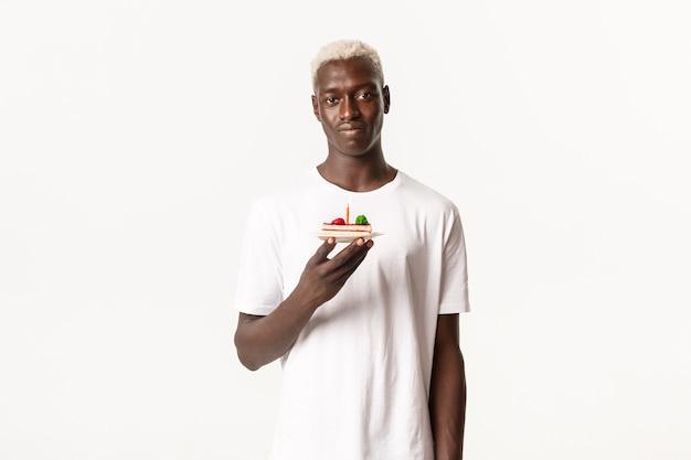 Porträt des düsteren afroamerikanischen jungen blonden mannes, der geburtstagstorte mit kerze hält und widerstrebend schaut