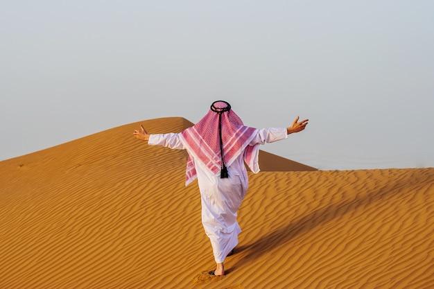 Porträt des durstigen arabischen mannes auf einer mitte der gelben wüste.