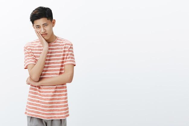 Porträt des einsamen verärgerten und gelangweilten jungen männlichen asiatischen studenten mit dunklem kurzen haarschnitt, der kopf auf handfläche lehnt und mit düsterem gleichgültigem blick schaut, der langweiligen film zur linken seite des kopierraums sieht