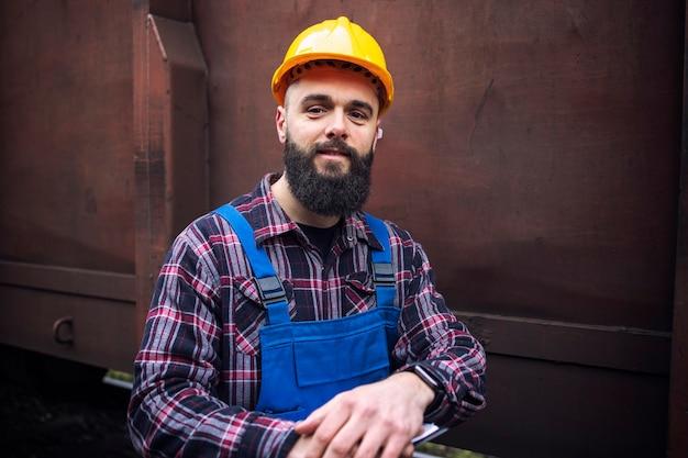 Porträt des eisenbahnarbeiters, der durch zuggüterwagen steht
