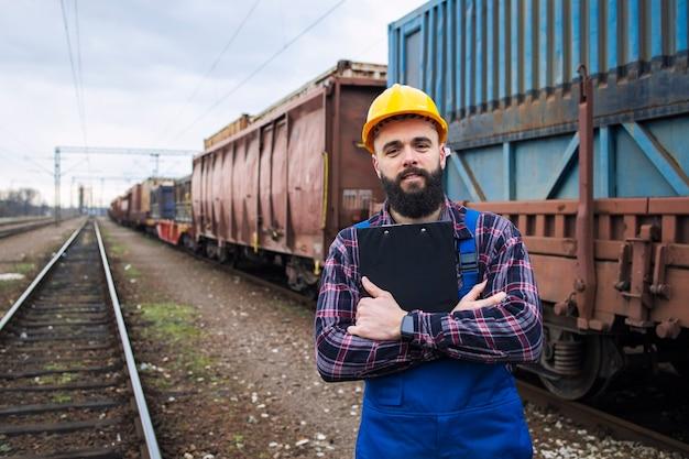 Porträt des eisenbahnvorarbeiters, der checkliste hält und frachtversand kontrolliert