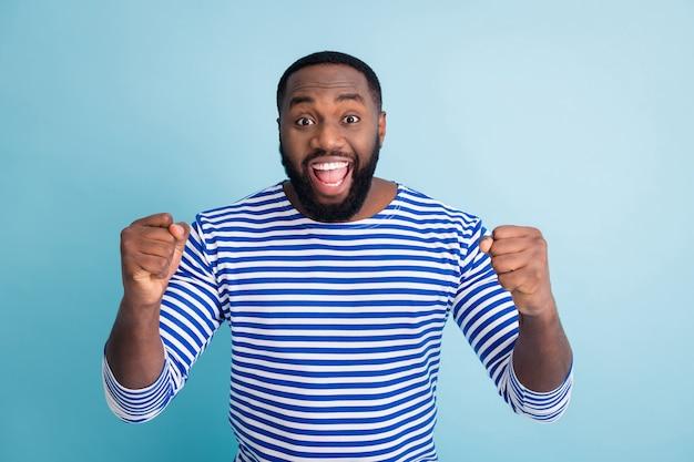 Porträt des ekstatischen fröhlichen afroamerikaners feiern frühlingszeit-feiertagslotteriegewinn erhöhen fäuste schreien ja tragen sie trendige stilvolle seemannskleidung, die über blauer farbwand isoliert wird
