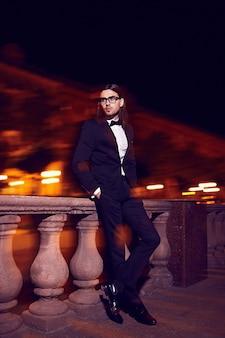 Porträt des eleganten langhaarigen jungen mannes der mode. attraktives und hübsches männliches model im schwarzen anzug mit schnurrbart auf der straße bei nacht