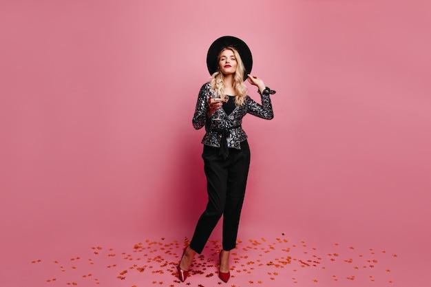 Porträt des eleganten mädchens in den roten schuhen, die champagner trinken. hübsche blonde frau mit schwarzem hut.