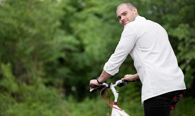 Porträt des eleganten mannes, der glücklich ist, fahrrad zu fahren