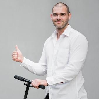 Porträt des eleganten mannes, der glücklich ist, roller zu fahren