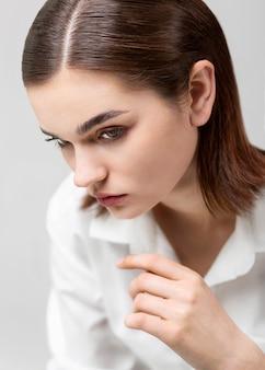 Porträt des eleganten weiblichen modells, das im weißen hemd aufwirft. neues weiblichkeitskonzept