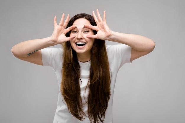 Porträt des emotionalen glücklichen modells, das im studio in camera schaut vorführt das täuschen steht