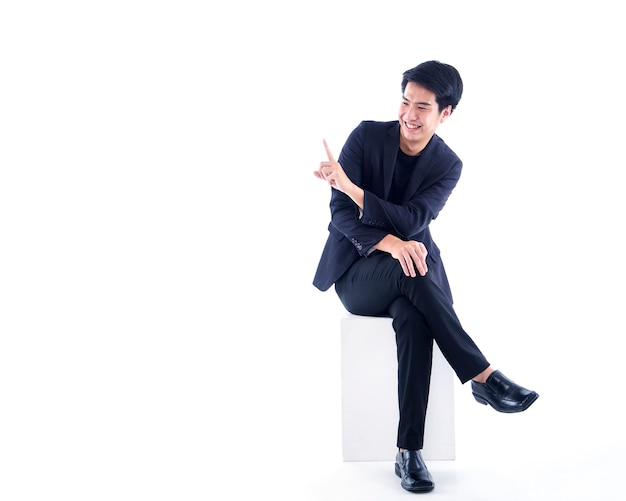 Porträt des emotionalen gutaussehenden mannes, der finger auf weiße wand mit kopienraum zeigt