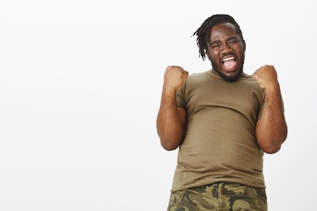 Porträt des energetischen kerls in einem braunen t-shirt, das gegen die weiße wand aufwirft