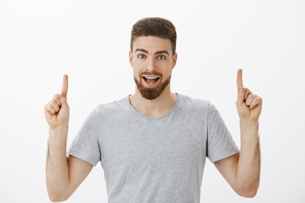 Porträt des enthusiastischen und aufregenden abgehenden brunet-mannes mit bart im grauen lässigen t-shirt, das die hände hebt, die nach oben zeigen und erstaunlichen kopienraum aufwärts diskutieren, der gegen weiße wand aufwirft