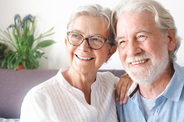 Porträt des entspannenden sitzens des älteren paares zu hause auf sofa. gelassene ältere menschen, die den ruhestand genießen