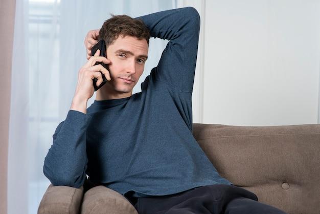 Porträt des entspannten gutaussehenden kerls, der junge mann liegt und sitzt bequem auf einer couch oder einem sofa zu hause