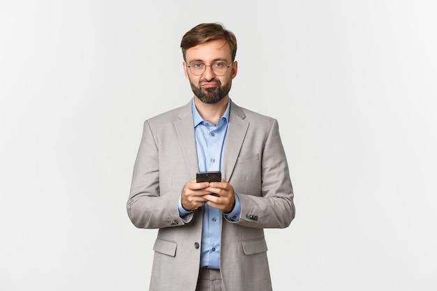 Porträt des enttäuschten bärtigen mannes im geschäftsanzug und in der brille, smartphone haltend